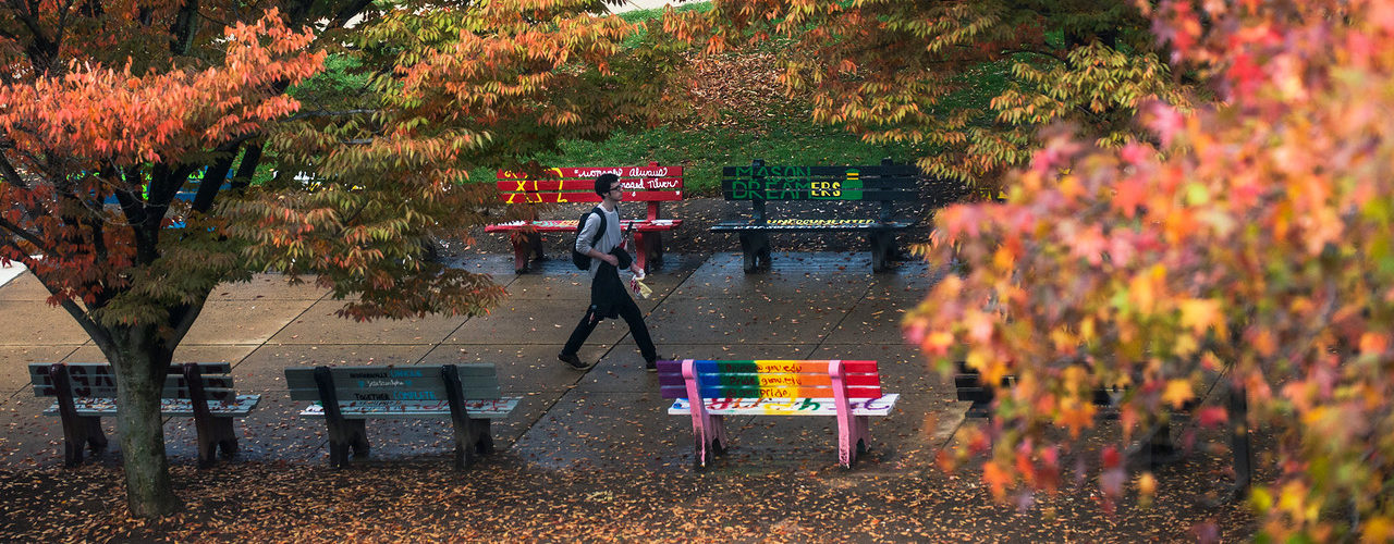 Students walking in front of the student benches in the Fall. Photo by Evan Cantwell/George Mason University